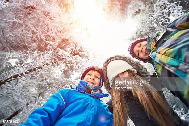 Happy winter kids in frozen forest