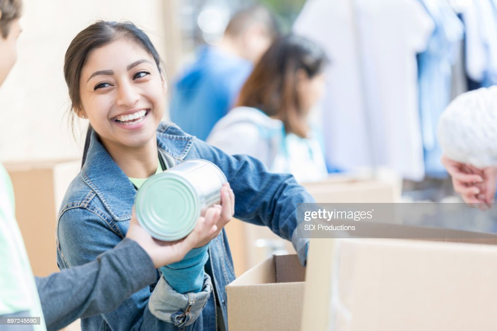 Happy woman accepts food donations during food drive : Stock Photo
