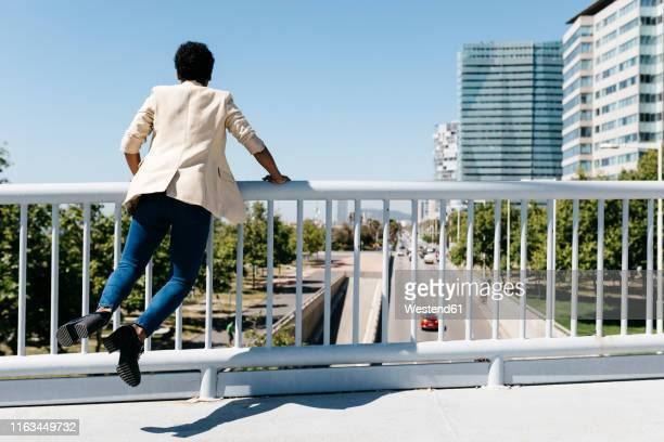 happy woman after work jumping, office buildings in the background - 歩道橋 ストックフォトと画像