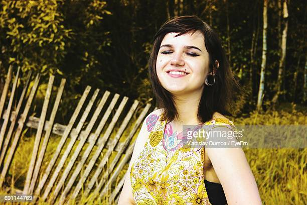 Happy Woman Against Damaged Fence