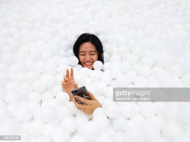 Happy Woman Amidst White Balls Using Phone In Pool