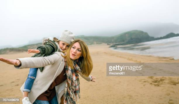 Happy woman and daughter pretending to fly on the beach in winter
