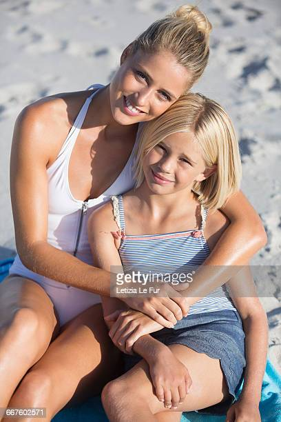 Happy woman and her daughter sitting on the beach