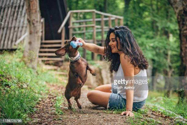 幸せな女性と彼女の犬の遊び - イヌのおもちゃ ストックフォトと画像