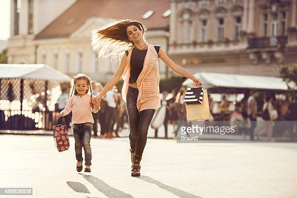 Happy woman and little girl running with shopping bags.