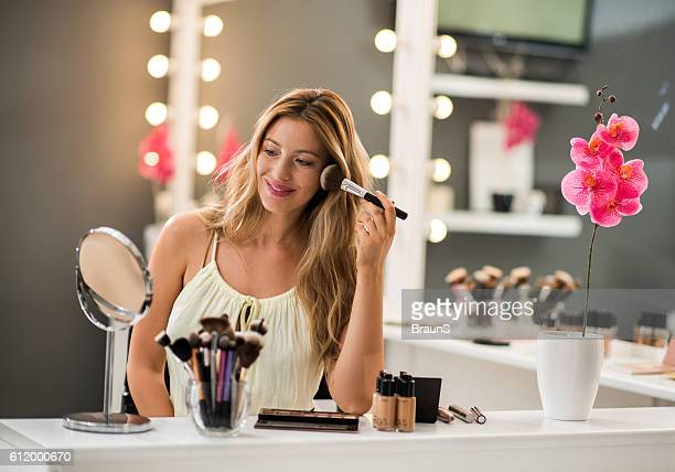 Happy woman applying face powder with make-up brush.