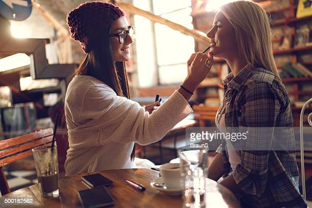 Happy woman applying make-up on her friend's lips.