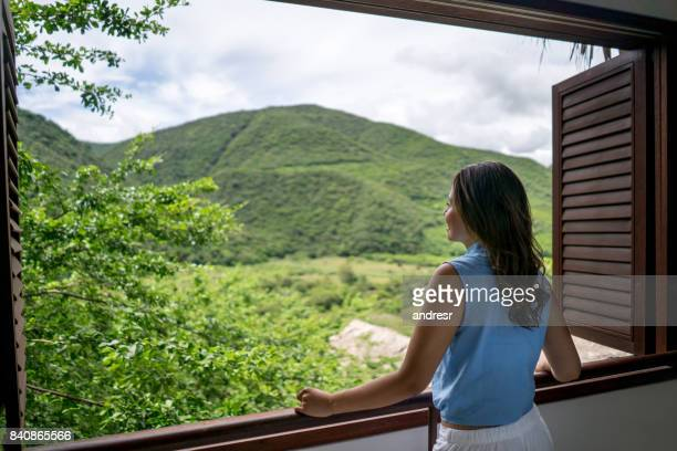 happy woman at a hotel looking at the view from her room - hostel stock pictures, royalty-free photos & images
