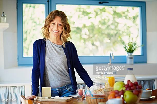 happy woman at breakfast table in kitchen - 40 44 años fotografías e imágenes de stock