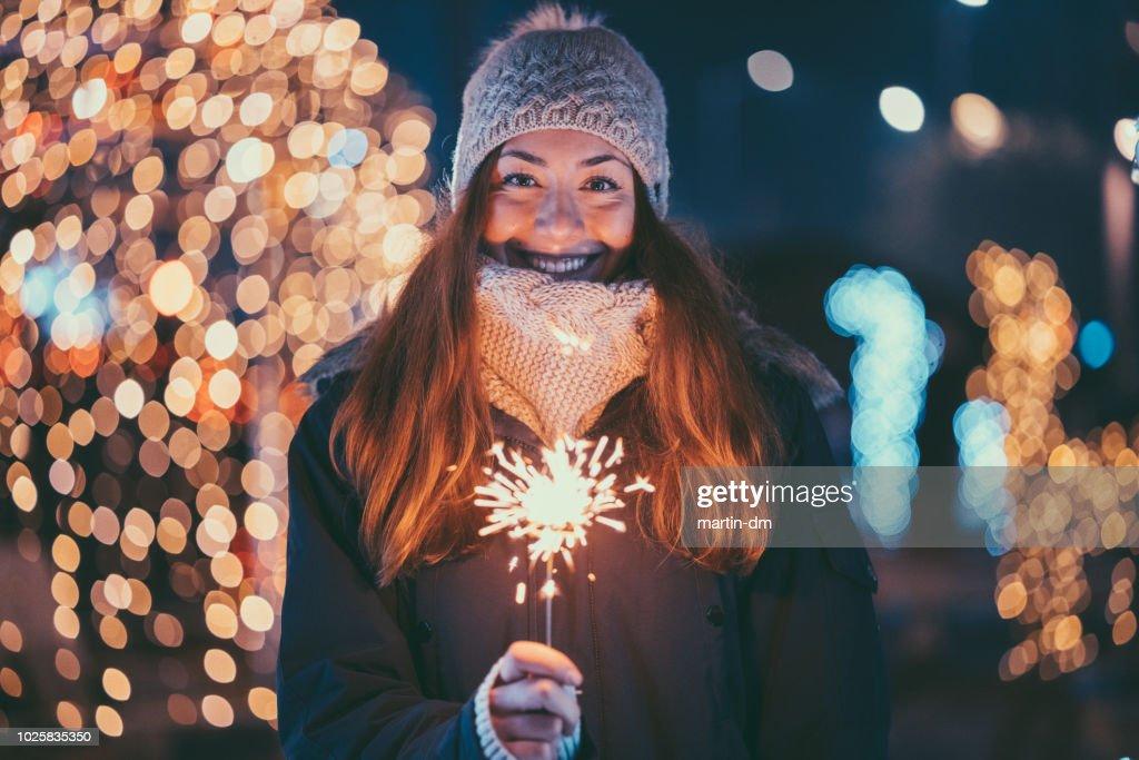 Happy woman at Christmas holding burning sparkler : Stock Photo