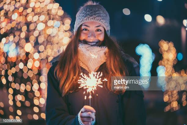 happy woman at christmas holding burning sparkler - december stock pictures, royalty-free photos & images