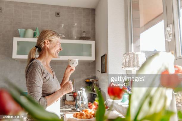 Happy woman at home in kitchen looking out of window