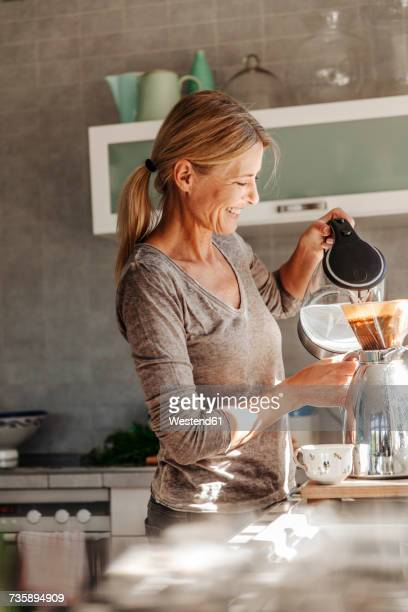 Happy woman at home in kitchen preparing coffee