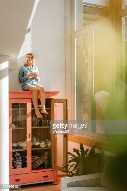 Happy woman at home sitting on cupboard with cup of coffee