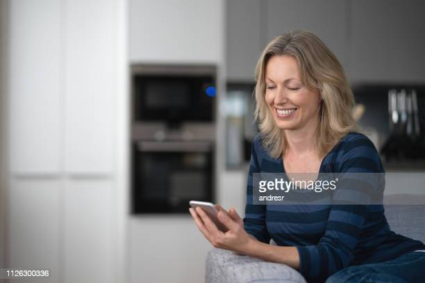 happy woman at home using app on her cell phone - one mature woman only stock pictures, royalty-free photos & images