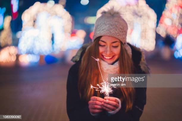 happy woman at new year's eve holding burning sparkler - new year stock pictures, royalty-free photos & images