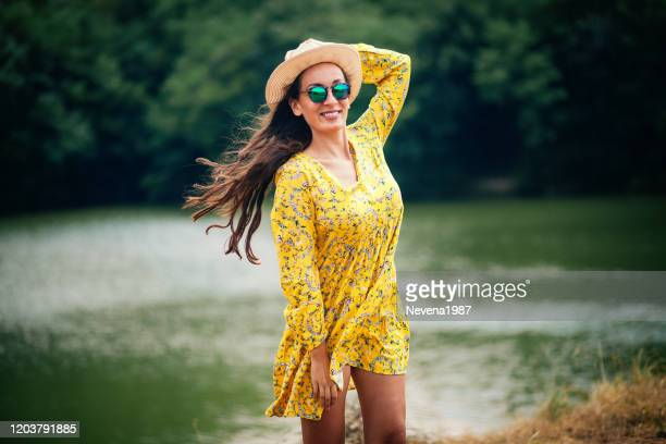 happy woman at river - floral pattern dress stock pictures, royalty-free photos & images