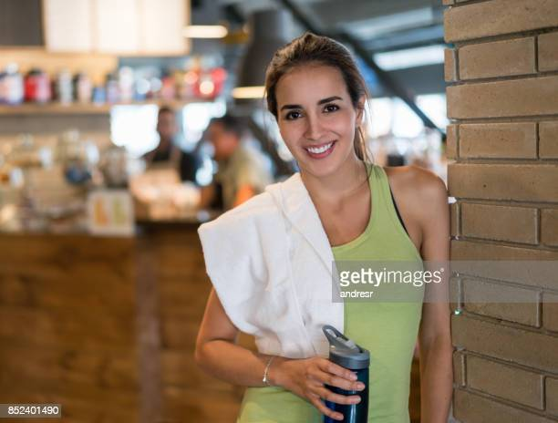 Happy woman at the gym drinking water