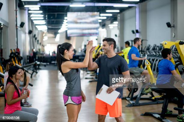 Happy woman at the gym giving a high-five to her trainer