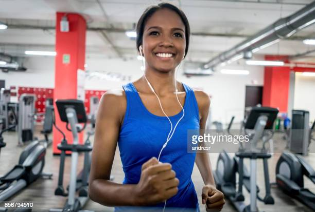 Happy woman at the gym listening to music while running