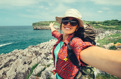 Happy woman backpacker traveler take a selfie photo on amazing ocean coast 956864266