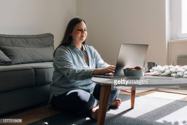 happy woman blogging from home on her laptop computer at christmastime - voluptuous stock pictures, royalty-free photos & images