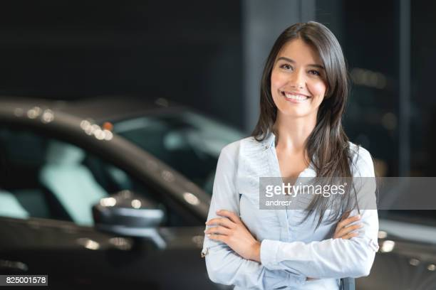 happy woman buying a car at the dealership - happy merchant stock pictures, royalty-free photos & images