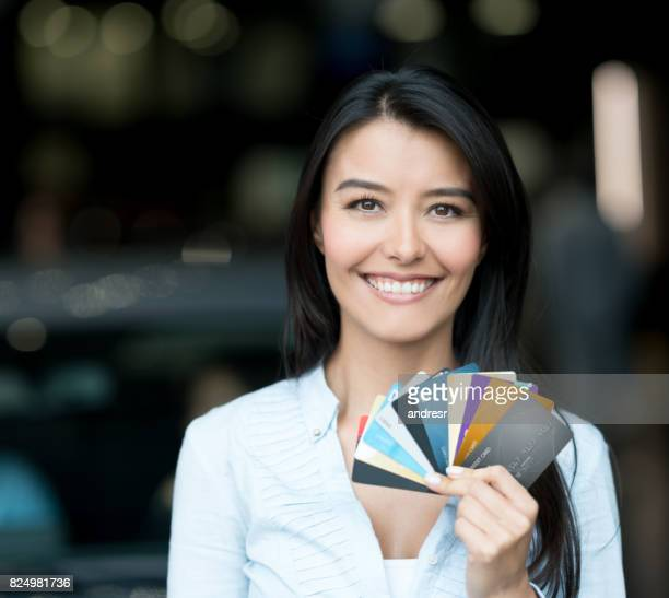 Happy woman buying a car at the dealership with credit cards