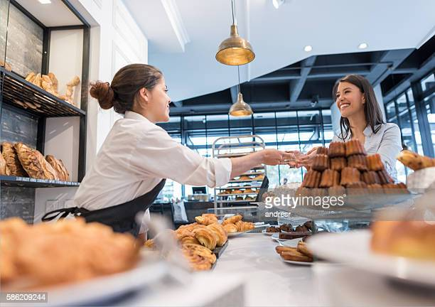 happy woman buying pastries at a bakery - bakery stock pictures, royalty-free photos & images