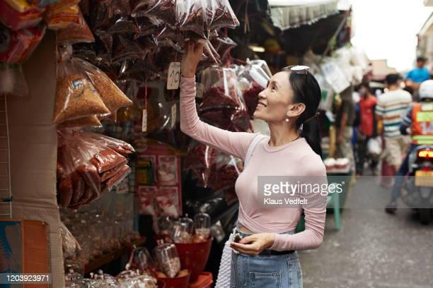 happy woman buying spices at market - une seule femme d'âge mûr photos et images de collection