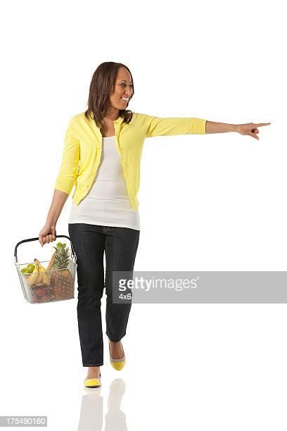 Glückliche Frau tragen einem Korb von Obst und zeigt