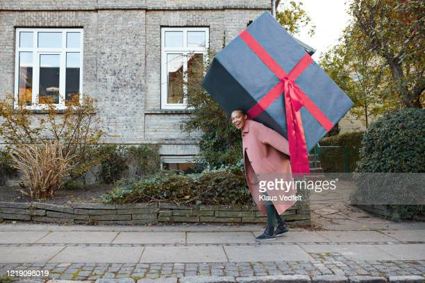 happy woman carrying large gift box on footpath - clothing stock pictures, royalty-free photos & images