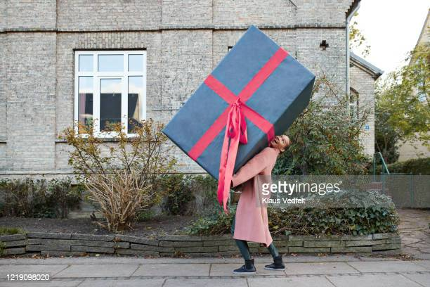 happy woman carrying large gift box on footpath - cadeau photos et images de collection