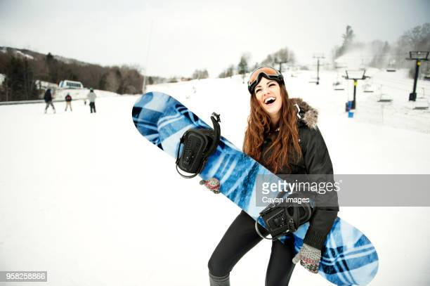 Happy woman carrying ski on snow covered mountain