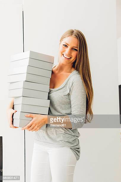 Happy woman carrying stack of boxes