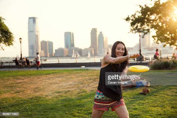 Happy woman catching plastic disc while standing in park against clear sky
