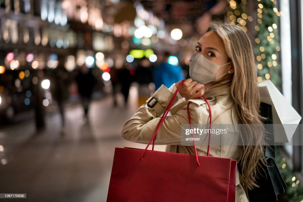 Happy woman Christmas shopping wearing a facemask : Stock Photo