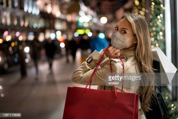 happy woman christmas shopping wearing a facemask - merchandise stock pictures, royalty-free photos & images