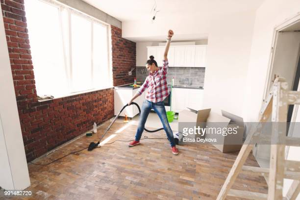 Happy woman cleaning with vacuum cleaner her new home