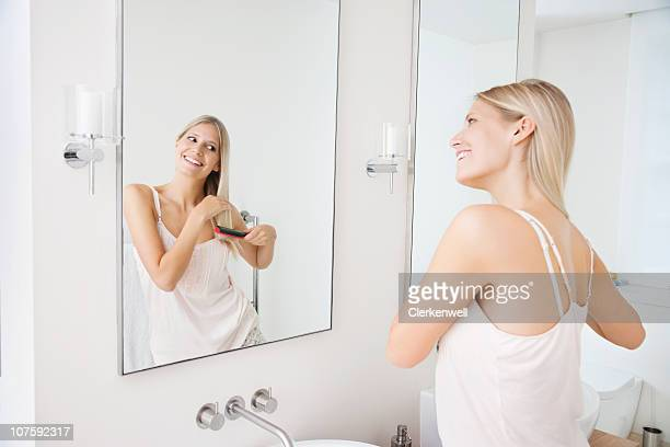 Glückliche Frau Kämmen das Haar vor Badezimmerspiegel