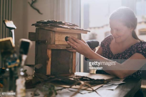 happy woman constructing a bird house. - vogelhäuschen stock-fotos und bilder
