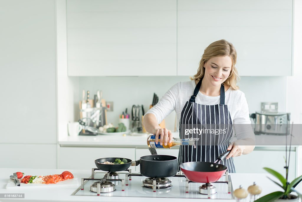 Happy Woman Cooking At Home High-Res Stock Photo - Getty