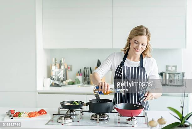 happy woman cooking at home - grembiule foto e immagini stock