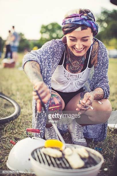 Happy woman cooking on a barbecue at picnic