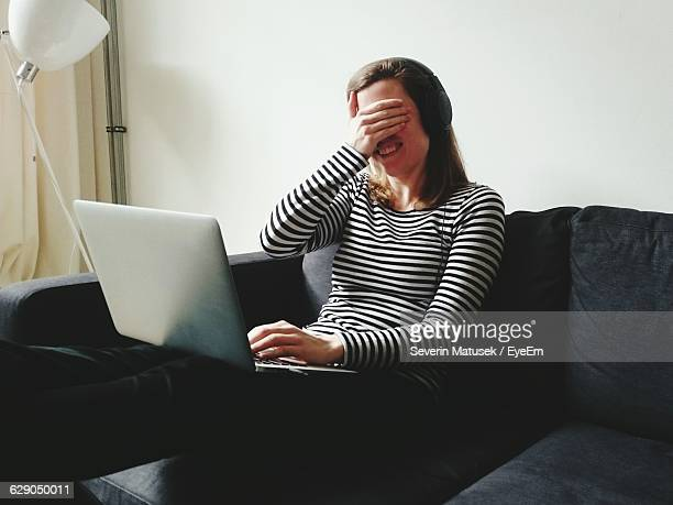 Happy Woman Covering Eyes While Video Chatting Through Laptop At Home