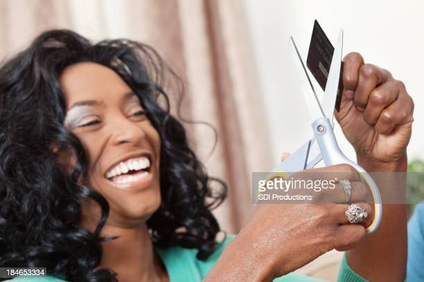 Happy woman cutting up her credit card