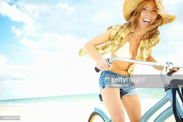Happy woman cycling on beach
