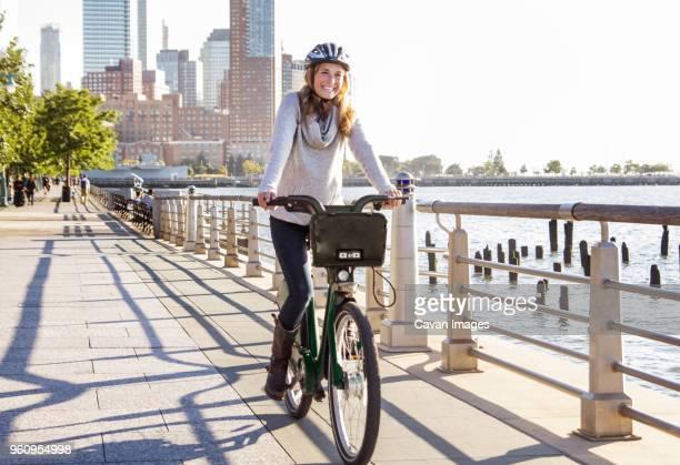 happy woman cycling on bridge by river in city - casque de protection au sport photos et images de collection