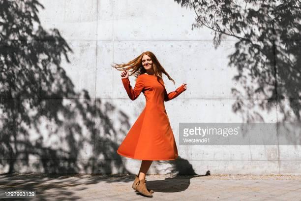 happy woman dancing against tree shadow wall - 回転する ストックフォトと画像