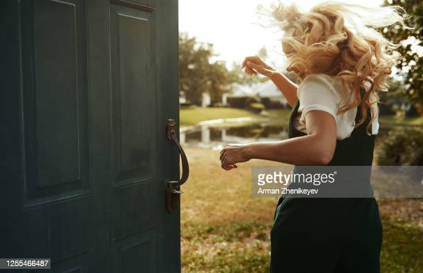 happy woman dancing and jumping next to the open door. nicely fits for book cover - runaway stock pictures, royalty-free photos & images